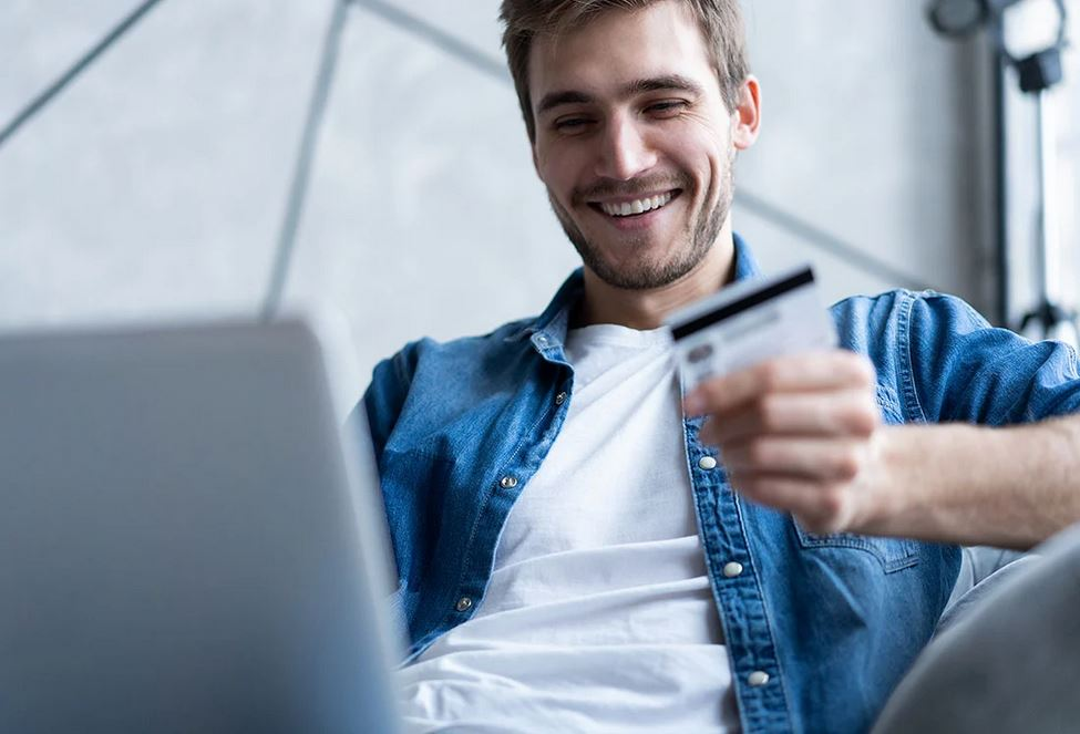 man sitting at computer holding credit card
